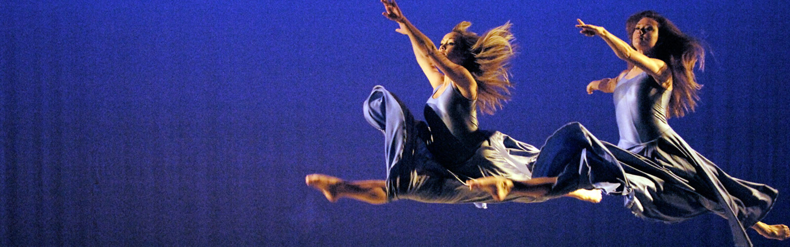 two female dancers on state in purple dresses mid split leap.