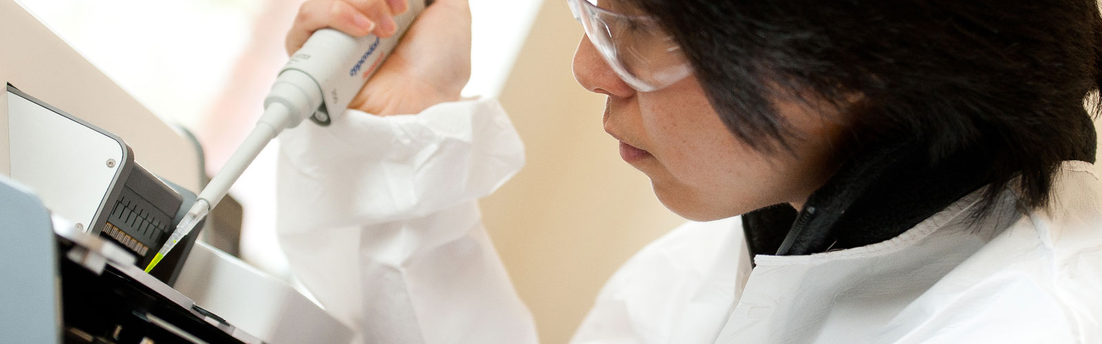 woman in lab coat working with chemicals