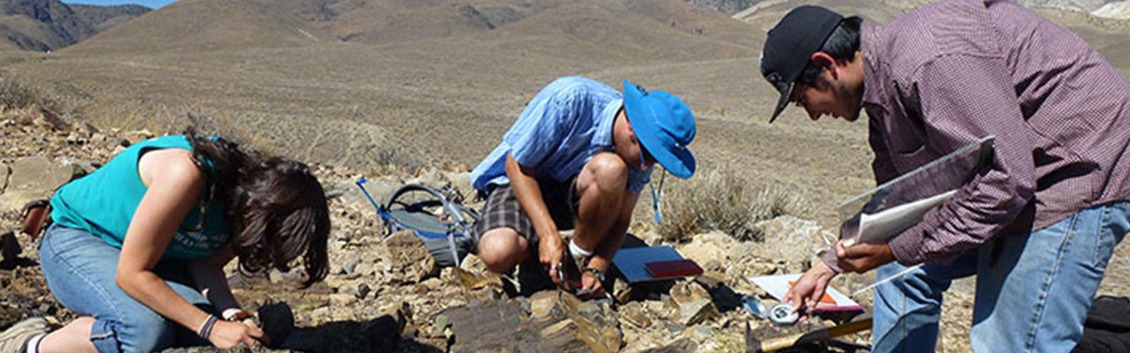 3 people examining rocks on desert floor