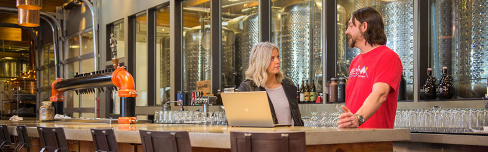 man and woman talking at a bar