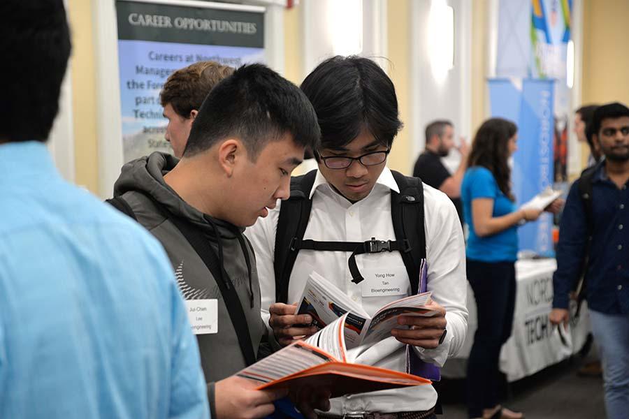 Students reading handbooks at the career fair