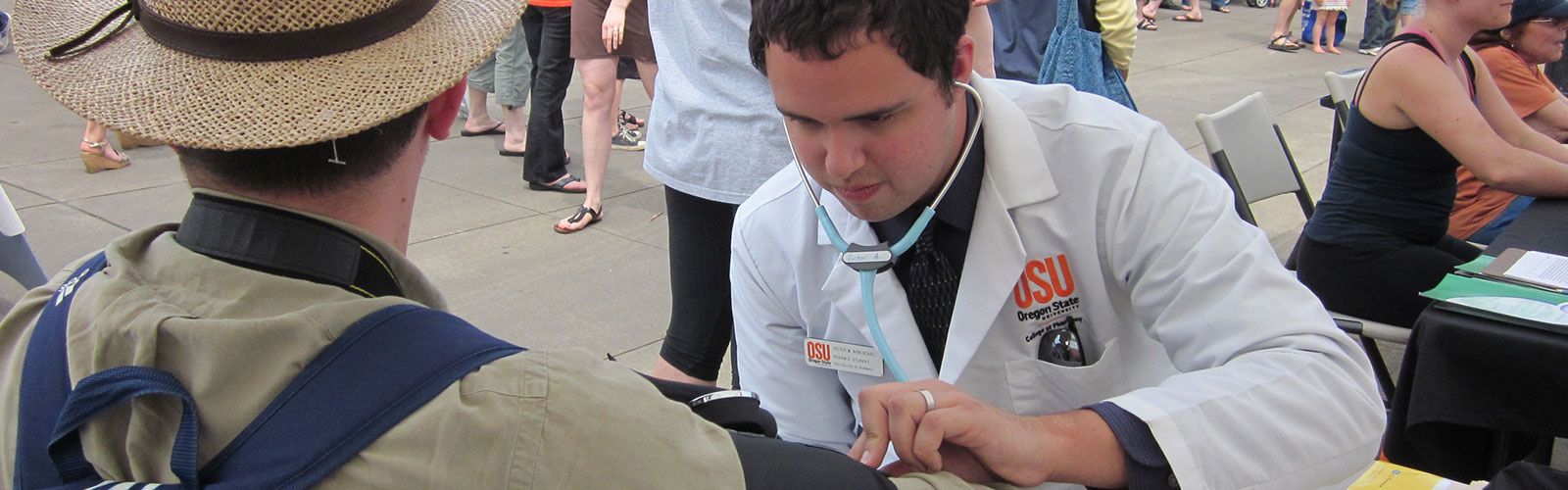 student in white lab coat conducting blood pressure test