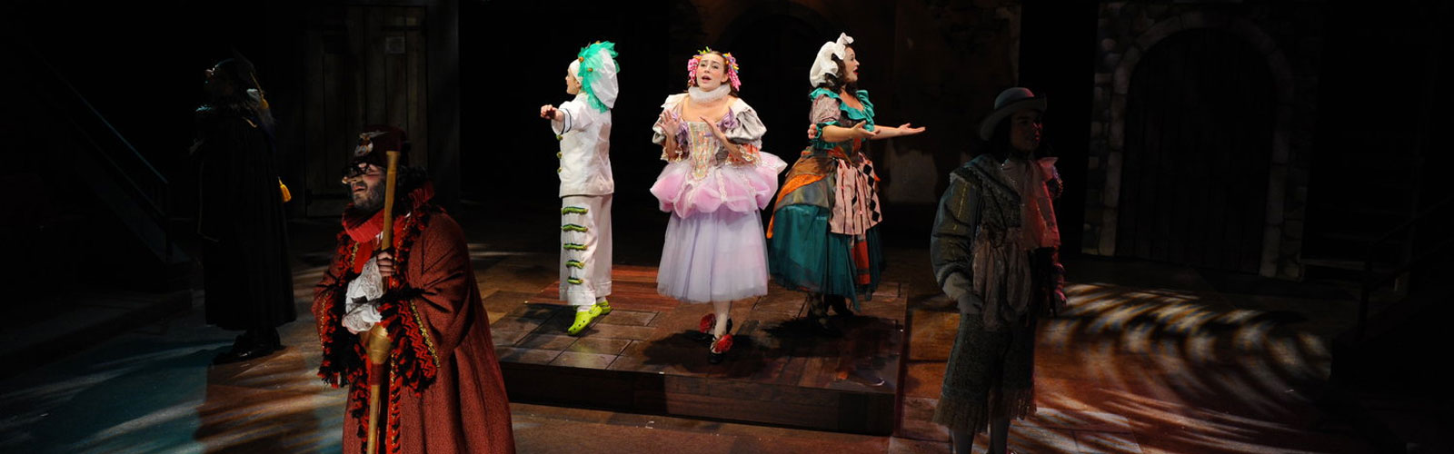 students in colorful costumes acting on a stage